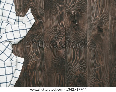 View from above on brown wooden table with linen kitchen towel or textile napkin. Blue tablecloth on dark brown wood tabletop. Copy space for text. Can use as mock up for design #1342719944