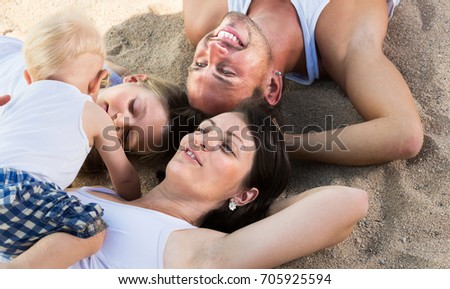 View from above on glad parents with two children relaxing on beach #705925594