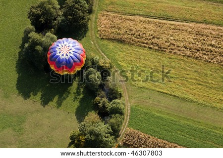 View from above on the hot air balloon flying over the fields and creek.