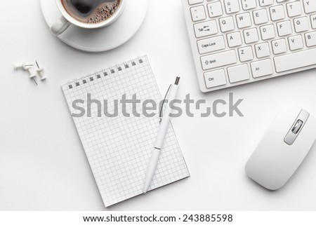 view from above on white office table with notepad, computer and coffee cup