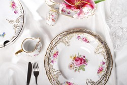 View from above over a table arrangement of a luxury porcelain dinnerware with golden hand painted floral design.