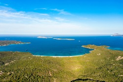 View from above, stunning aerial view of a green coastline with some beaches bathed by a turquoise sea. Liscia Ruja, Costa Smeralda, Sardinia, Italy.