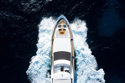 View from above, stunning aerial view of a luxury yacht cruising on a blue water creating a wake. Costa Smeralda, Sardinia, Italy.