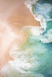 View from above, stunning aerial view of a person relaxing on a beautiful beach bathed by a turquoise sea during sunset. Kelingking beach, Nusa Penida, Indonesia.