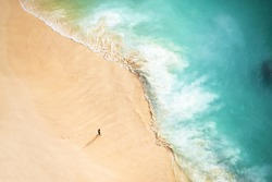 View from above, stunning aerial view of a person walking on a beautiful beach bathed by a turquoise sea during sunset. Kelingking beach, Nusa Penida, Indonesia.