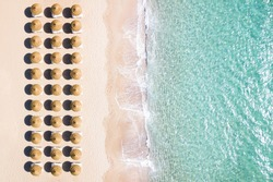 View from above, stunning aerial view of an amazing white beach with beach umbrellas arranged symmetrically and a beautiful turquoise clear water. Sardinia, Italy.