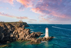View from above, stunning aerial view of an old and beautiful lighthouse located on a rocky coast bathed by a rough sea. Faro di Capo Ferro, Porto Cervo, Sardinia, Italy.