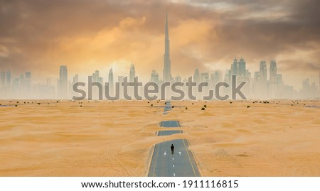 View from above, stunning aerial view of an unidentified person walking on a deserted road covered by sand dunes with the Dubai Skyline in the background. Dubai, United Arab Emirates.