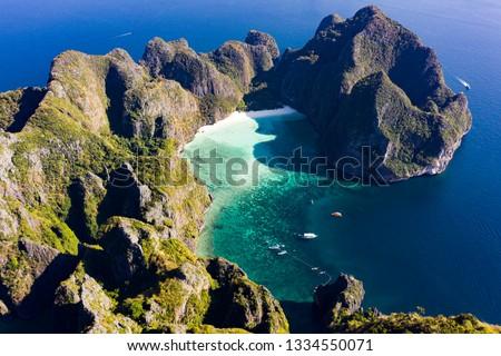 View from above, stunning aerial view of Koh Phi Phi Leh (Phi Phi Island) with the beautiful Maya Bay. A turquoise and clear water bathes a white beach surrounded by limestone mountain.
