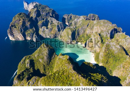View from above, stunning aerial view of Koh Phi Phi Leh (Phi Phi Islands) with the beautiful Maya Bay. A turquoise and clear water bathes a white beach surrounded by limestone mountains.