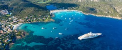 View from above, stunning aerial view of the Grande Pevero beach with boats and luxury yachts sailing on a turquoise, clear water. Sardinia, Italy.