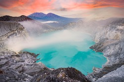 View from above, stunning aerial view of the Kawah Ijen volcano complex at sunset with the blue acid lake and some clouds of toxic gases raising from a sulfur deposit. East Java, Indonesia.