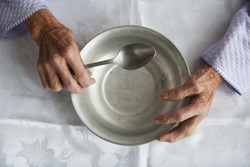 View from above.The hands of an old grandmother of 90 years are holding an empty aluminum bowl and spoon, poverty and poverty, the hunger of the older generation.