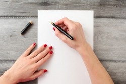 View from above to woman's hands with red nails, holding black fountain ink pen with gold nib, ready to write something on empty piece of paper laying on gray wood table.