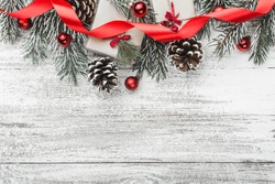 View from above, top, on a white wooden board background with evergreen, fir branch with pines, gift, present boxes, ribbon and red tree globes with space for text, greeting card