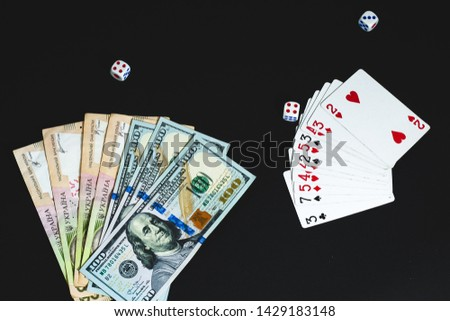 View from above. View from above. large notes dollars and hryvnia on a black background. Money, dices and cards  #1429183148
