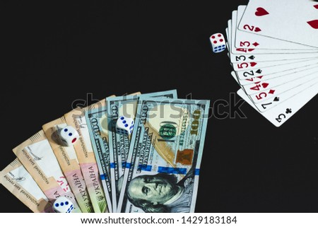 View from above. View from above. large notes dollars and hryvnia on a black background. Money, dices and cards  #1429183184