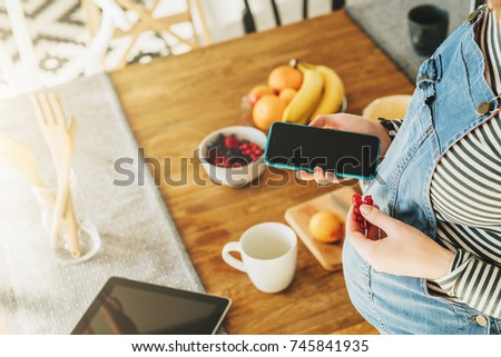 View from above. Young pregnant woman is standing in kitchen near table, eating berries and using smartphone. On table is digital tablet, fruit, dishes. Girl browsing internet, chatting, blogging. #745841935