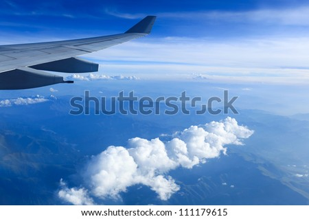 view from airliner window with white clouds and mountain range - stock photo