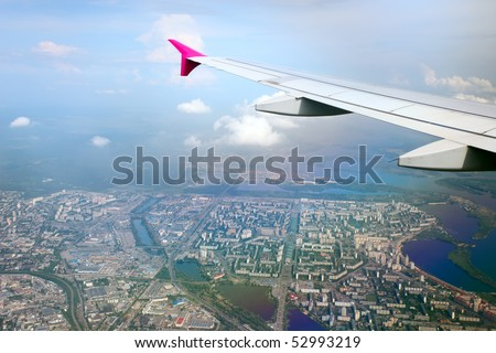 View from airplane of the wing and panorama of a city beneath