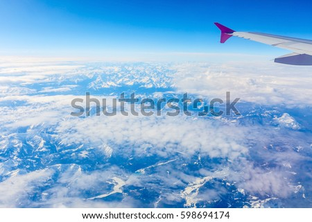View from airplane window of alps and blue sky on nice sunny day #598694174