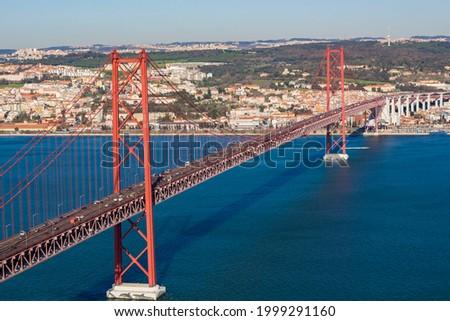 View from Almada of suspension  Ponte 25 de Abril bridge (The 25th April Bridge) over river Tejo Tagus in Lisbon, Portugal. Bridge alike Golden gate in Portugal.  Foto stock ©