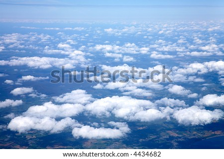 View from an aeroplane window, flying above white clouds over Ireland.
