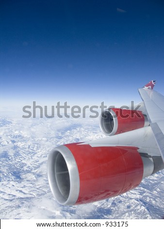 View from an aeroplane window of the red engines over some mountains with a deep blue sky.