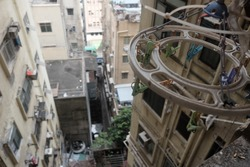 View from an old apartment in Hong Kong. Clothes hangers with pastel-colored clips.