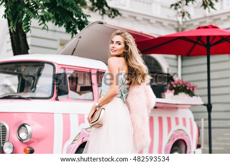 View from back fashion model in tulle skirt on  retro coffee car background. She has long blonde hair, wears pink stole on shoulder, smiling to camera