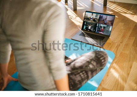 View from back of a woman having virtual yoga class with group of people at home on a video conference. Fitness trainer taking online yoga classes over a video call in laptop.