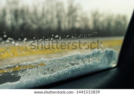 View from backseat of a car while looking outside car window with snow deposited on its edges and blurry dried trees in the background.