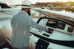 View from behind of a mature bearded black guy in a hat and striped summer costume, starting the engine of his luxury yacht moored on marine, pushing the buttons on the modern dashboard