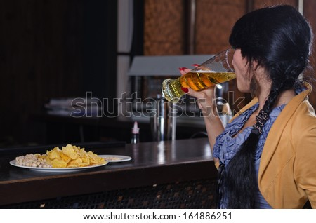 View from behind of a young woman gulping down a pint beer at the bar during Happy Hour with a plate of snacks on the counter in front of her