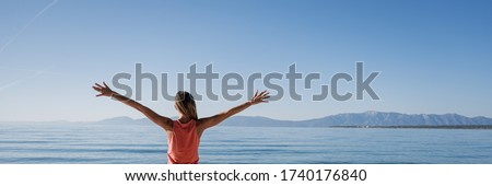 View from behind of a young woman in pink dresds standing by the calm morning sea with her arms spread widely as she greets the new day. Wide view image. Stock photo ©