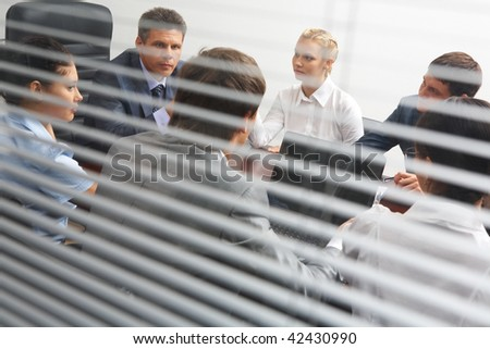 View from behind venetian blind of associates interacting at working meeting