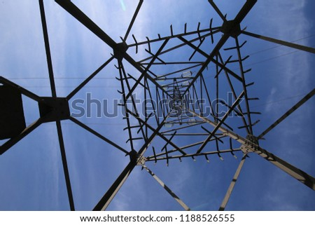 View from bellow of a high steel tower used to support electric cables. Abstract image with polygonal shapes and black lines. Blue cloudy sky in background. Symbolic picture with geometric design.