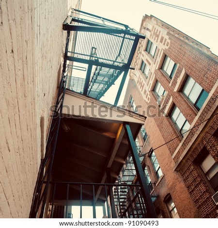 View from below a fire escape on a brick building.