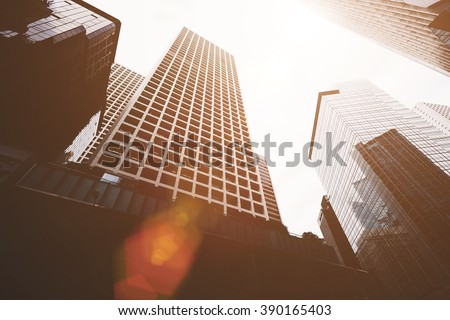 View from below of a high-rise buildings with contemporary architecture in business center in day. Tall modern skyscrapers against grey sky in big city #390165403