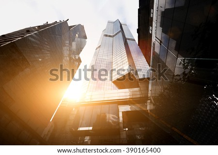 View from below of a tall skyscrapers in business district in sunny evening. Exterior of a modern office buildings in metropolitan city against beautiful sunset