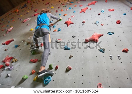 View from below of active guy during risky training on climbing wall