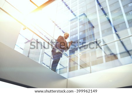 View from below of businessman is reading financial news on web page via cell telephone, while is standing in modern skyscraper interior. Confident male CEO is using mobile phone during work break
