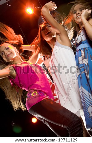 View from below of glamorous girls dancing at discotheque