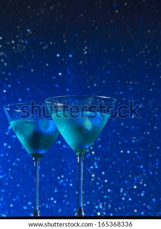 view from below of glasses of fresh blue cocktail with ice on blue tint light bokeh background like sky with star with space for text