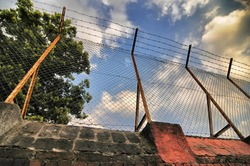 View from below of grunge wall and grid barbwire under blue cloudy sky