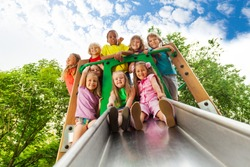 View from below of many kids on playground chute