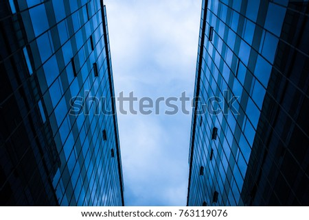 View from below of parallel tall skyscrapers in business district on cloudy day in Santiago, Chile. Futuristic atmosphere effect