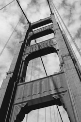 View from below of the Golden Gate Bridge in San Francisco (California). Black and white photography. High resolution. Cloudy day.