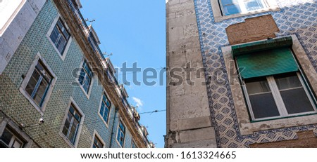 View from below of traditional Portuguese apartments with azulajos exteriors, or painted tiles. Taken on a sunny day in Lisbon, Portugal.
