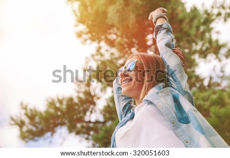 Shutterstock View from below of young beautiful happy woman with sunglasses and blue plaid shirt raising her arms over a sky and trees background. Freedom and enjoy concept.